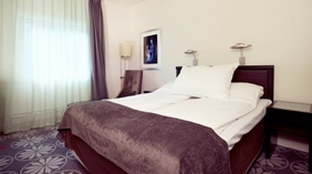 Large bed in double room at Aurora Hotel in Tromso