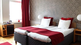 Family room with double bed and bedside lamps with minibar at Clarion Collection Hotel Bolinder Munktell Eskilstuna