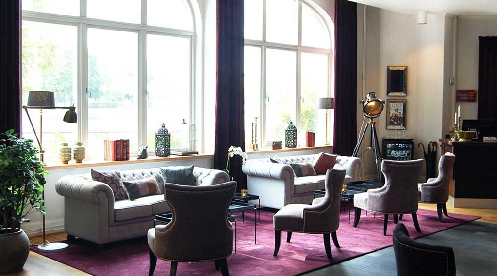 Lobby overview with chairs and sofas against the window at Clarion Collection Hotel Bolinder Munktell Eskilstuna