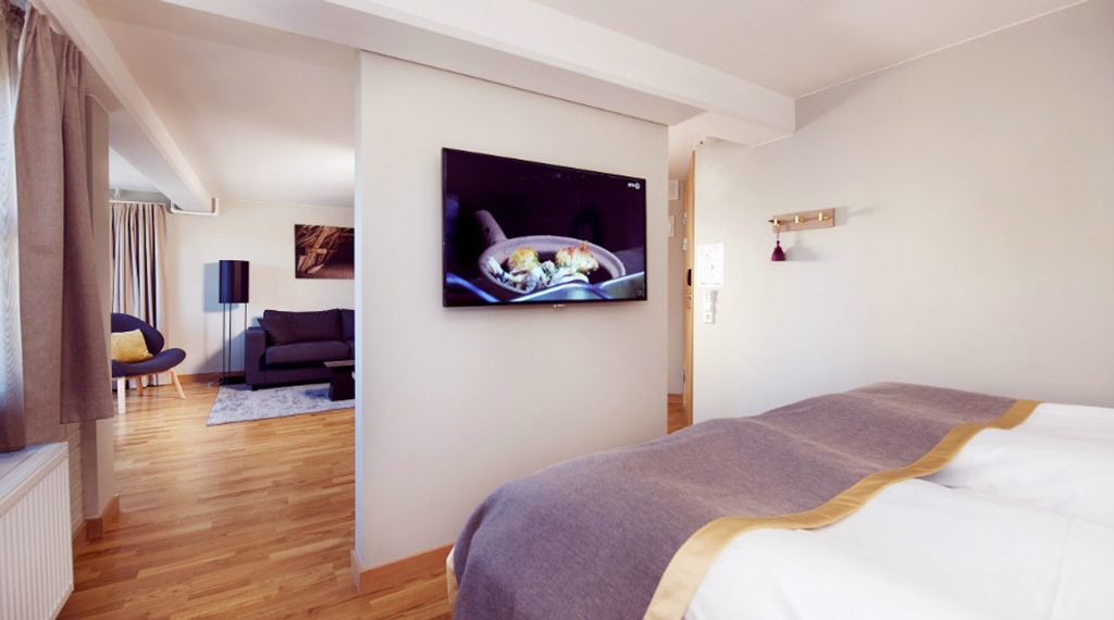 Double bed and TV in Deluxe room at Clarion Collection Hotel Bryggeparken