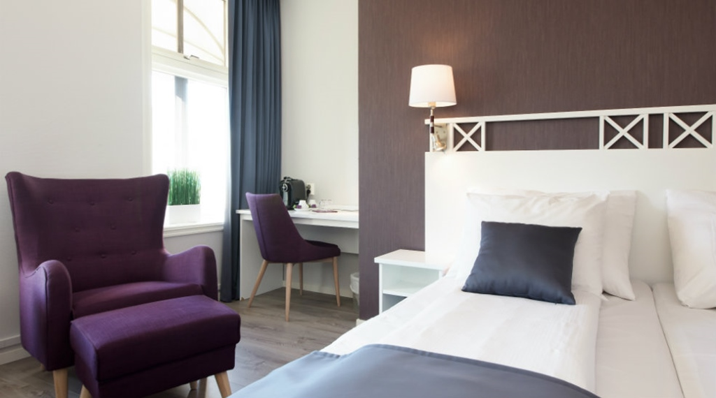 Bed and armchair in Superior double room at Clarion Collection Hotel Grand Gjøvik in Norway