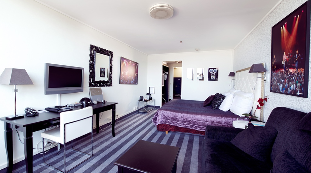 Stylish superior room with a desk, sofa and TV at Grand Olav Hotel in Trondheim