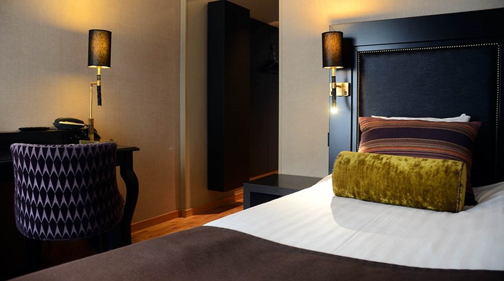 Standard single room bed with chair and lamp at Clarion Collection Hotel Grand Sundsvall
