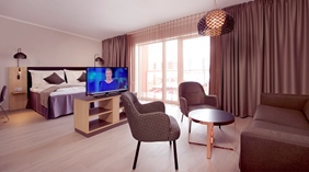 Deluxe double room with a bed, TV, lounge area and windows at the Clarion Collection Hotel Hammer