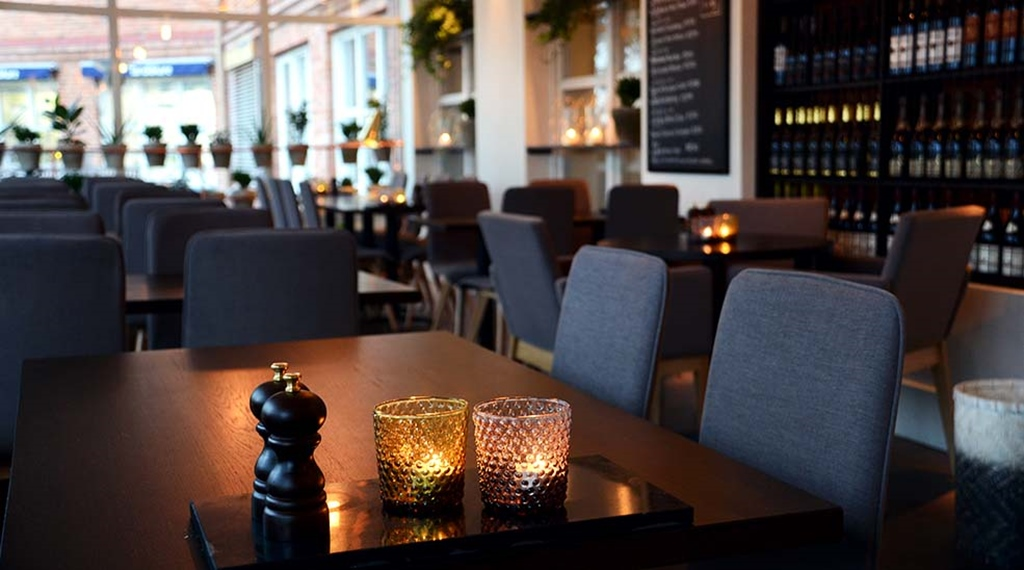 Restaurant seating area with candles at Clarion Collection Hotel Kompaniet Nyköping