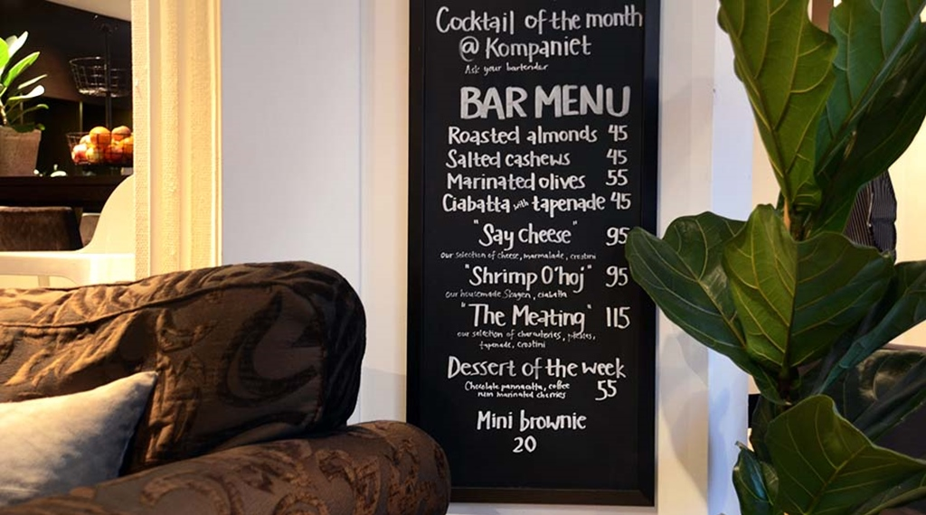 Bar menu in restaurant with chair and plant at Clarion Collection Hotel Kompaniet Nyköping