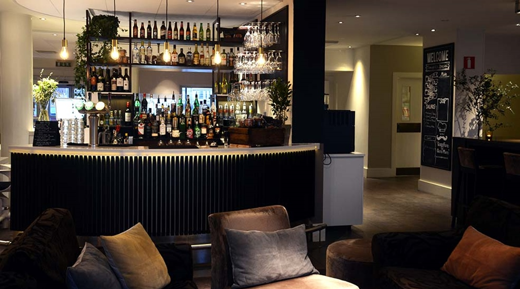 Bar overview in lounge with chairs at Clarion Collection Hotel Kompaniet Nyköping