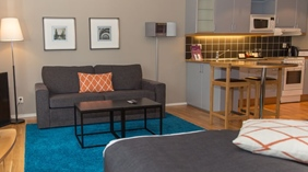 Family room with a bed, sofa and kitchen at the Clarion Collection Hotel Odin in Gothenburg