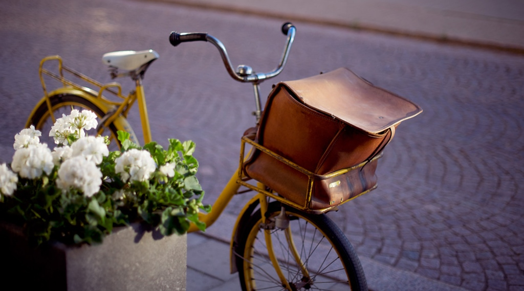 Outdoor interior including an elegant traditional yellow post bike at Post Hotel in Oskarshamn