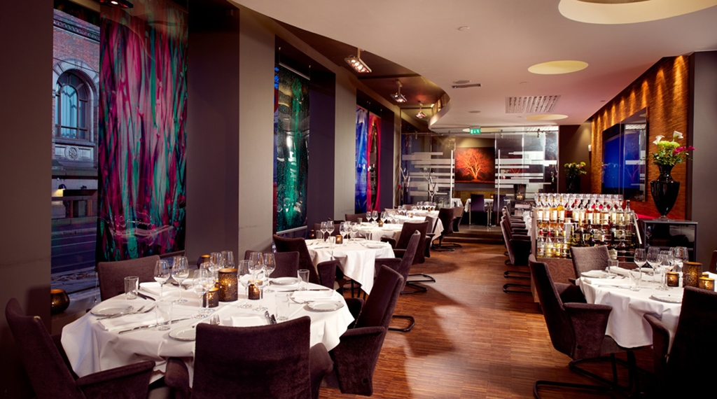 Stylish and colourful restaurant with high ceilings at Savoy Hotel in Oslo