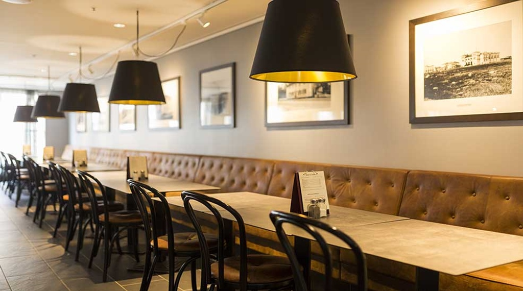 Restaurant with seating area with menu and lamps at Clarion Collection Hotel Uman Umeå