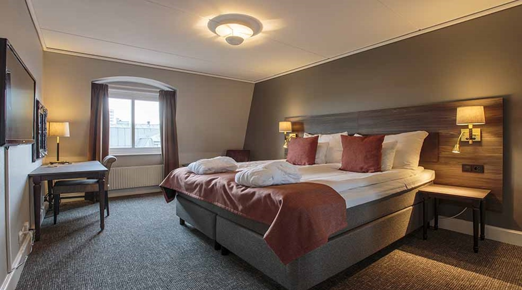 Suite double room with double bed and desk at Clarion Collection Hotel Uman Umeå