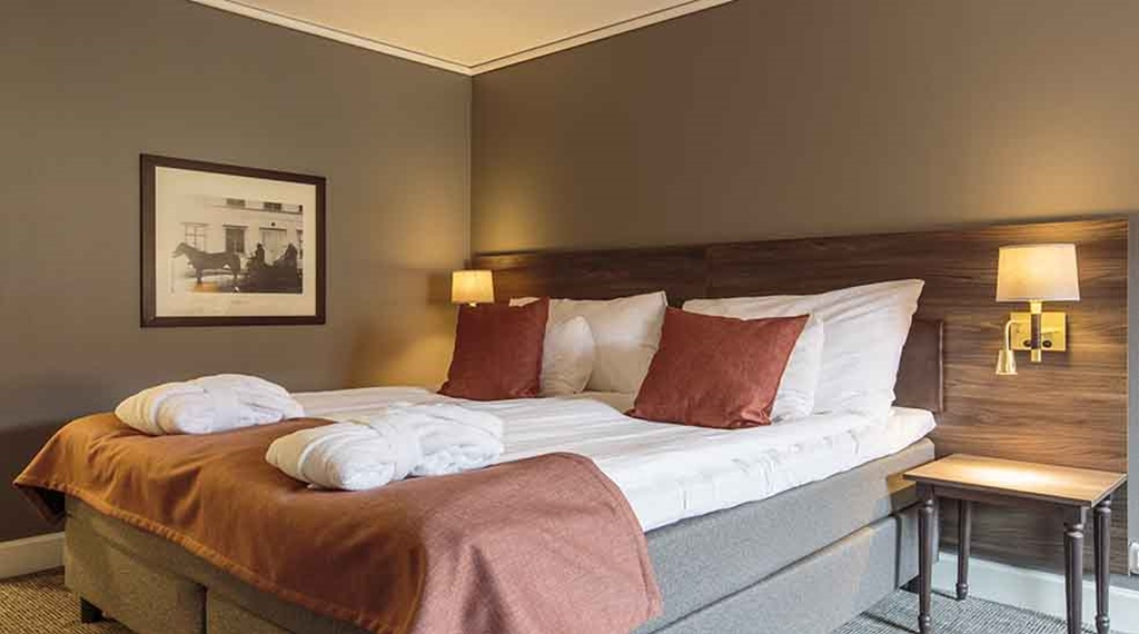 Superior double bed with robes at Clarion Collection Hotel Uman Umeå