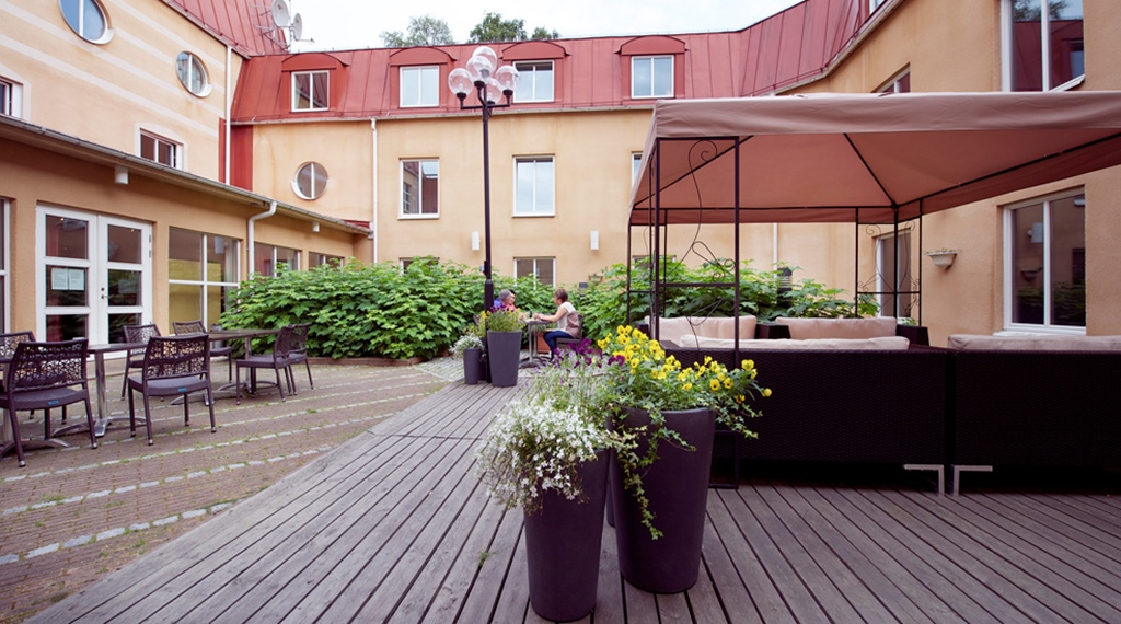 Spacious and open outdoor area with covered lounge at Uman Hotel in Umea