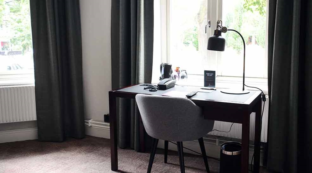 Suite with desk in front of window at Clarion Collection Hotel Victoria Jönköping