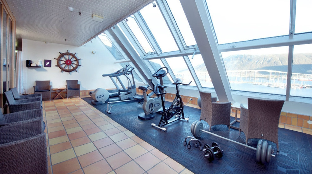 Well-equipped gym with large windows and a great view at With Hotel in Tromso