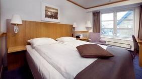 Well-furnished double room with an armchair at With Hotel in Tromso