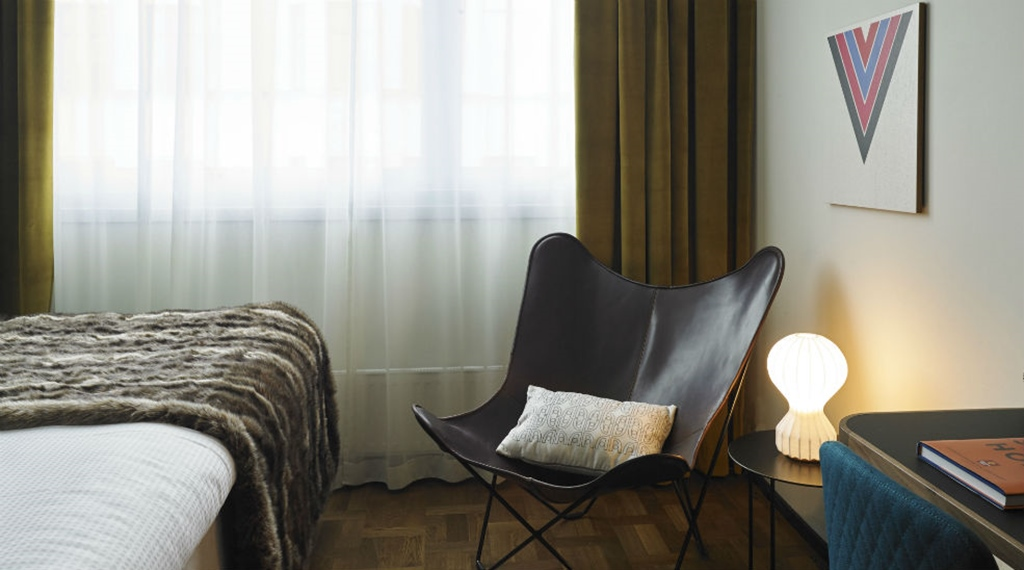 Bright single hotel room with designer chair at Amaranten Hotel in Stockholm