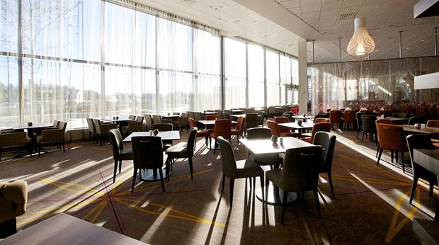 Extensive and bright restaurant dining area with high ceiling at Arlanda Hotel in Stockholm