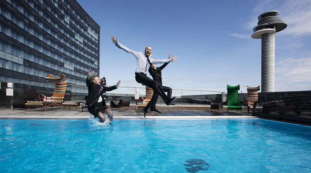 People jumping in the outdoor pool at Arlanda Hotel in Stockholm