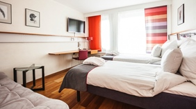 Spacious superior twin room with a sofa and flat screen TV at Grand Hotel in Ostersund