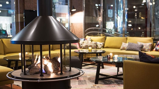 Lobby with comfortable seating and open fireplace at Hotel Orebro