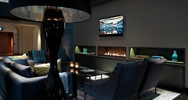 Trendy and cosy lounge area with open fireplace and flat screen TV at Post Hotel in Gothenburg