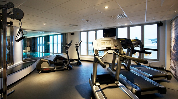 Spacious gym area with a view of the pool at Sense Hotel in Lulea