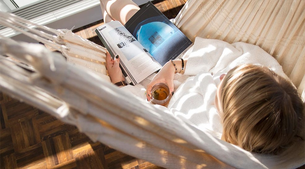 Woman with book and tea in hammock at Elements Spa at Clarion Hotel Stockholm