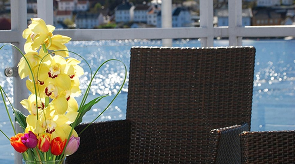 Relaxing terrace by the water outside the Kitchen & Table restaurant at Tyholmen Hotel in Arendal