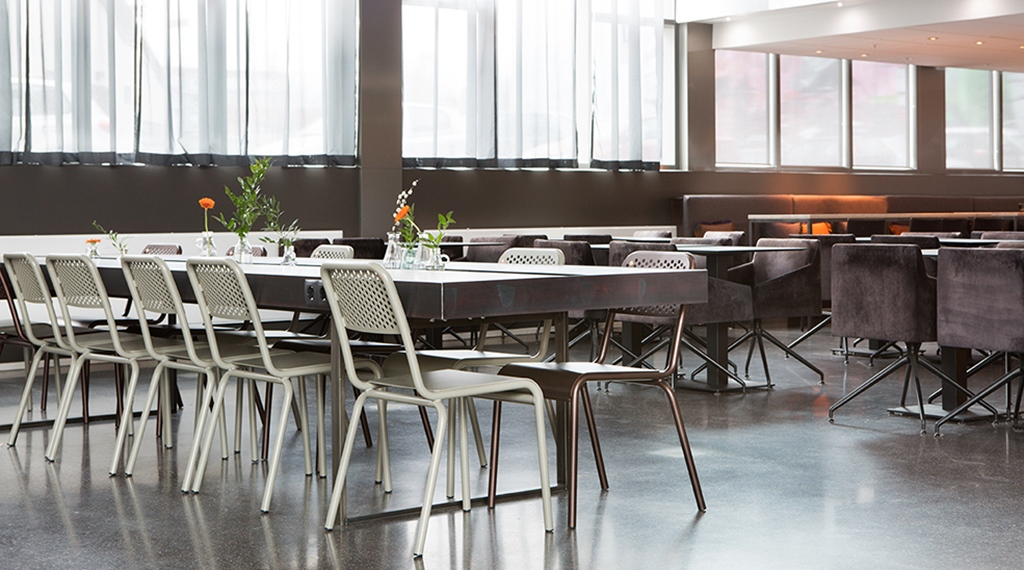 Lobby with community tables and metal chairs at Comfort Hotel Union Brygge in Drammen Norway
