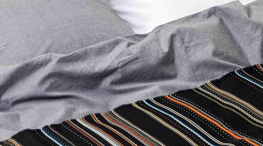 Grey bed-linen and multicolored blanket in hotel room at Hobo in Stockholm, Sweden