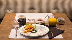 Breakfast with coffee, juice, yoghurt and sandwich on Finnish disgn plates at Hotel F6 in Helsinki, Finland