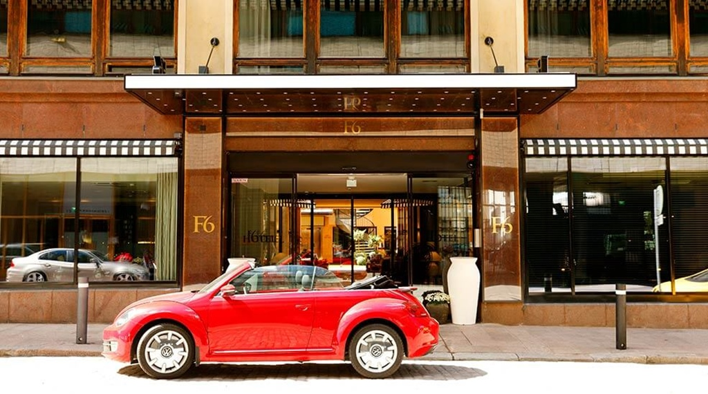 Red cabriolet parked in front of entrance to Hotel F6 in Helsinki, Finland