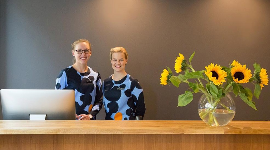 Two happy desk clerks at Hotel F6 in Helsinki, Finland