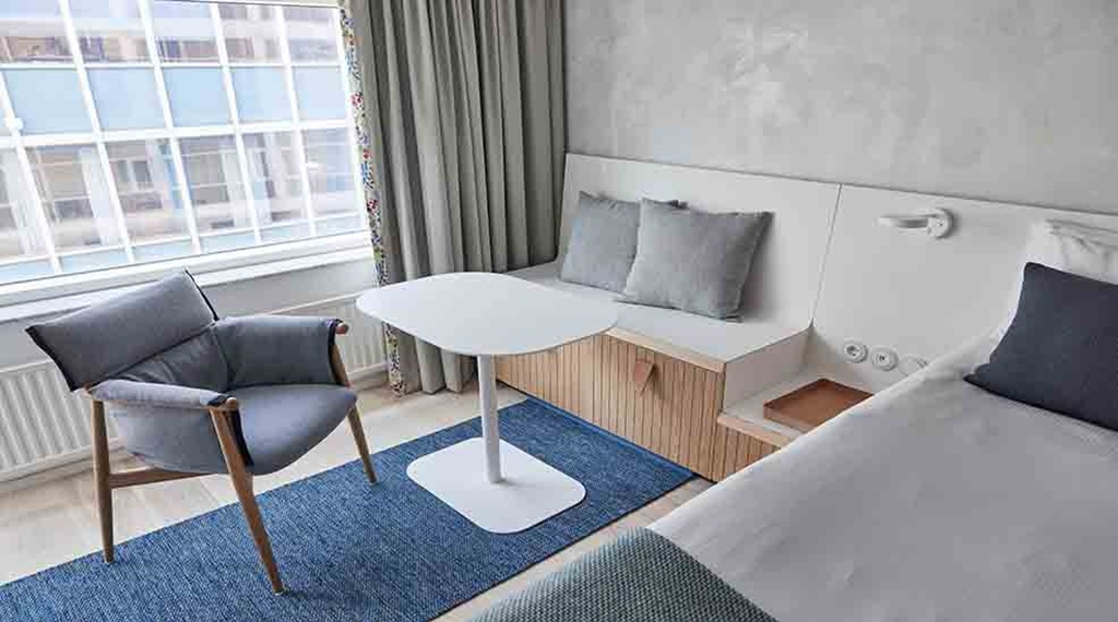 Seating area with table and chair in Scandinavian design in Superior Double hotel room with window at Nordic Light Hotel in Stockholm, Sweden