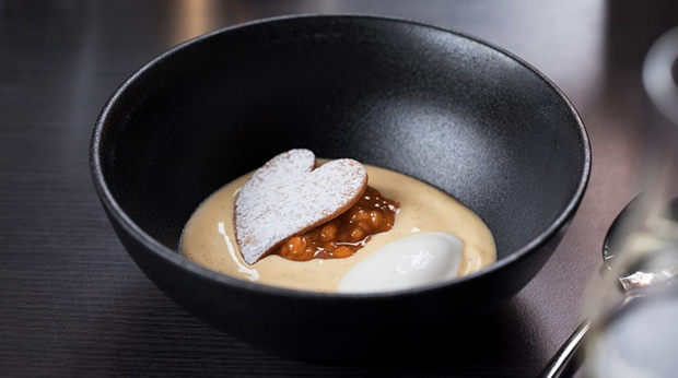 Black bowl with vanilla dessert and heart-shaped biscuit at the THIEF FOODBAR at THE THIEF in Oslo