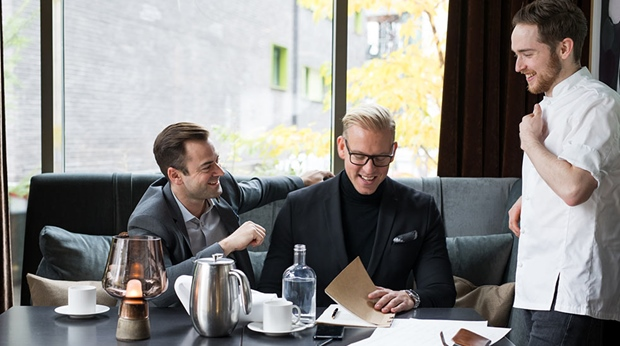 Two men and one waiter at table at Thief Foodbar at The Thief in Oslo