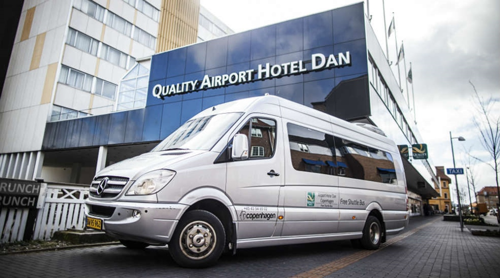 Airport shuttle bus and hotel façade at the Quality Airport Hotel Dan