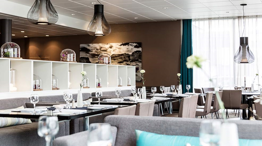 Dining area with a sofa, chairs and set table with wine glasses in the restaurant at the Quality Airport Hotel Værnes