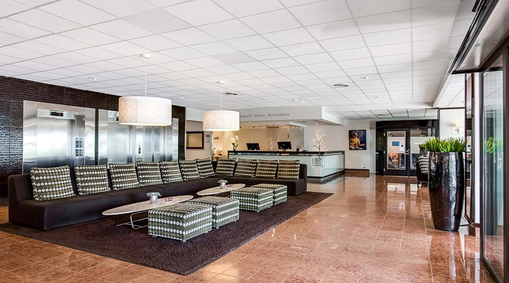 Lobby and reception area with sofas and lounge chairs, a rug, lamps and lifts at the Quality Hotel Alexandra