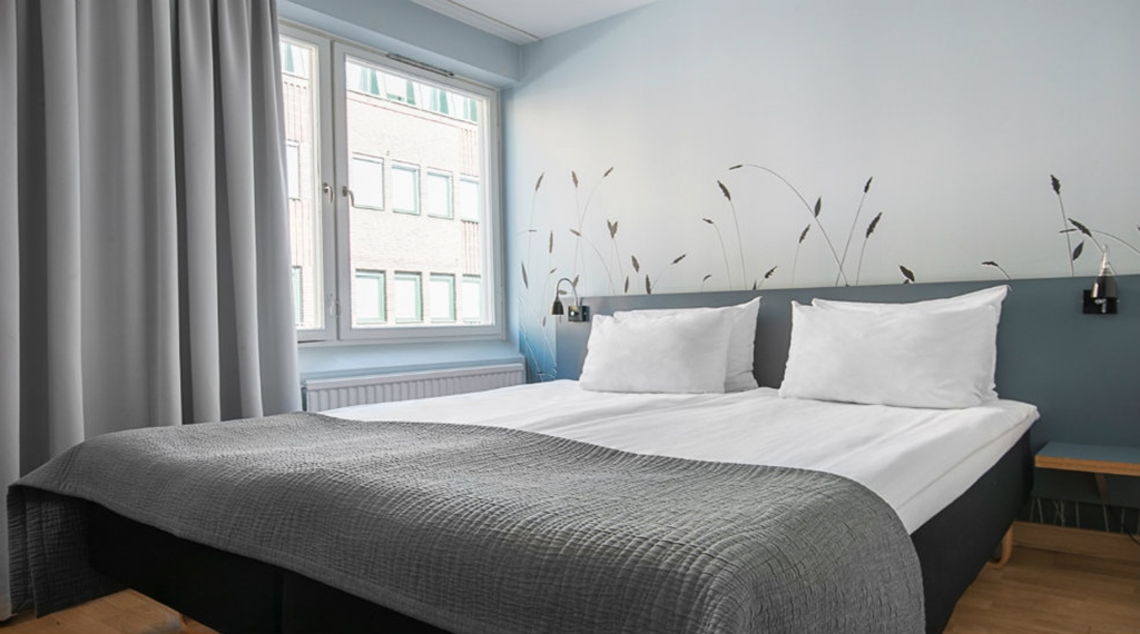 Modern standard double room with a double bed, grey bedspread, grey curtains and wall art at the Quality Hotel Grand Kristianstad