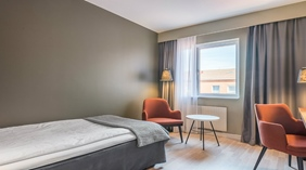 Standard single room with a bed, orange chairs, window, lamp and table at the Quality Hotel Grand Kristianstad