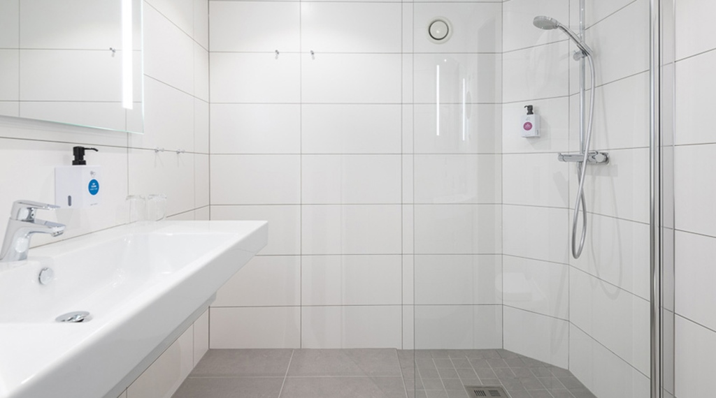 Tiled bathroom with a shower in a superior double room at the Quality Hotel Royal Corner