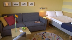 Neat standard single hotel room furnished with a desk, chair and sofa at Quality Hotel Vanersborg