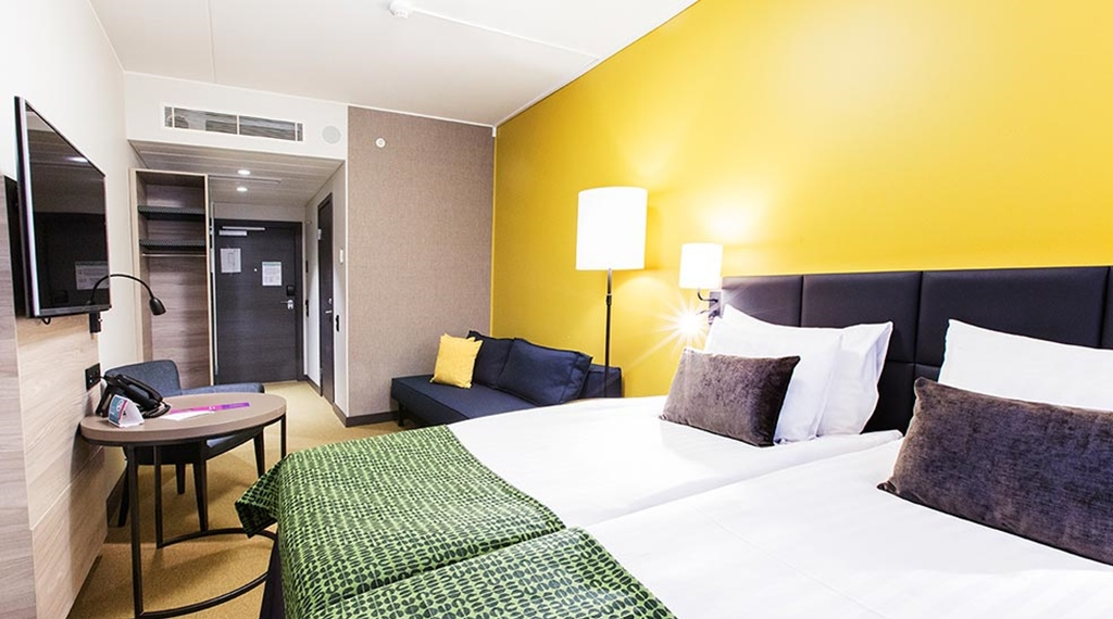 Superior double room with a double bed, soda, yellow walls and a seating area at the Quality Hotel Winn Haninge